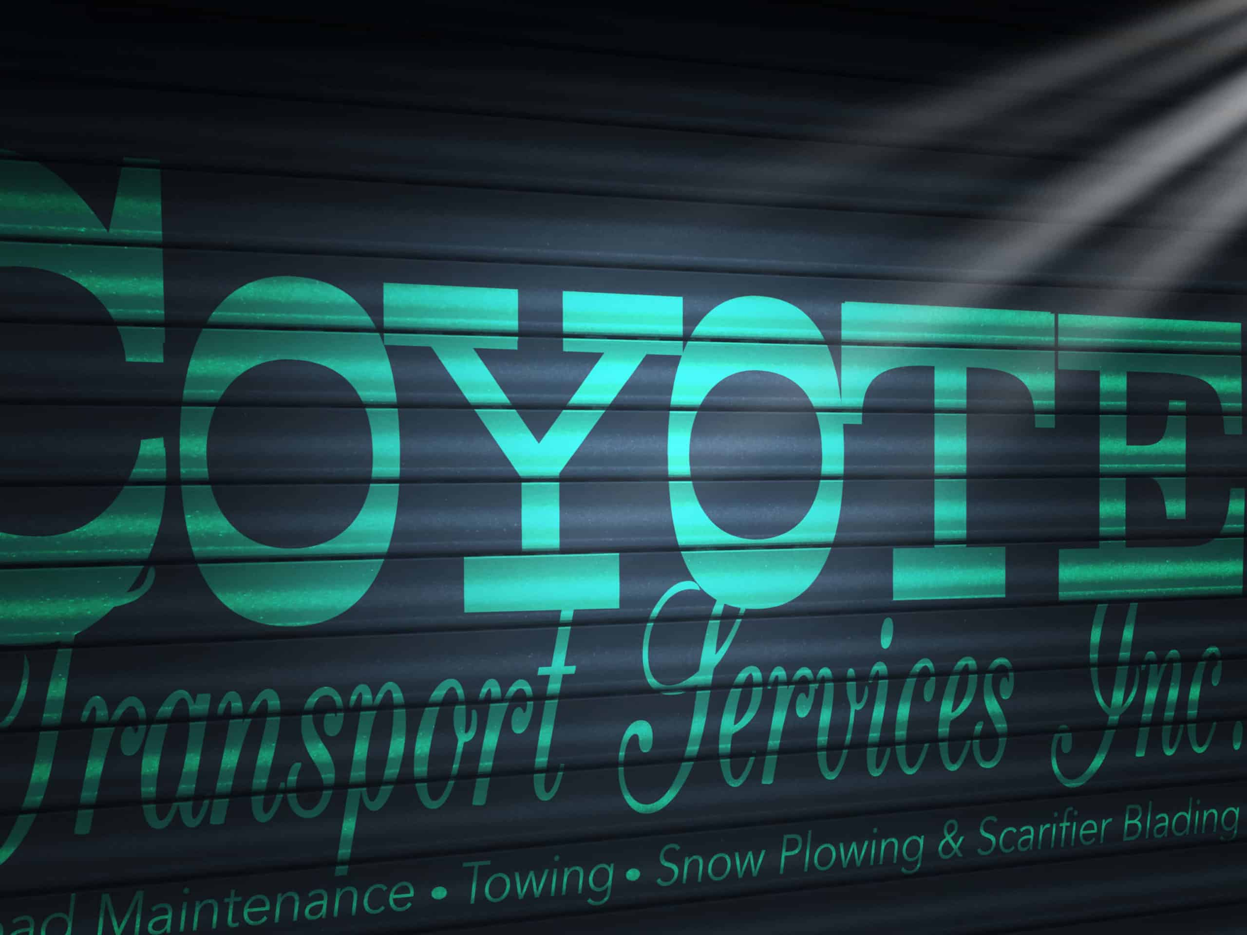 Coyote Transport Services Inc. logo in green mounted on garage door
